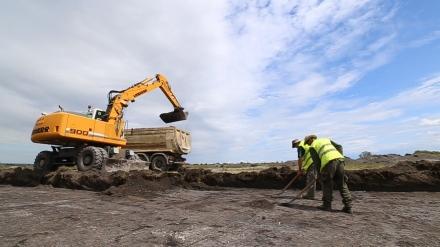 A humusztakaró eltávolítása gépi földmunkával régész felügyelete mellett zajlik. A gép nyomában haladva úgynevezett nyeséssel képeznek tükörfelületet, hogy a régészeti objektumok foltjai kirajzolódjanak a felszínen.